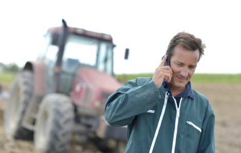 A farmer talking on a mobile phone in front of a tractor
