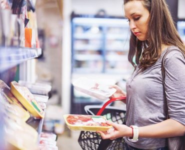 Consumer purchasing meat in supermarket